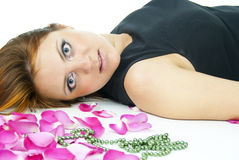 Portrait of a girl lying in rose petals Stock Photos