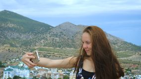 Portrait of a girl making selfie on the background of mountains and sky. stock video
