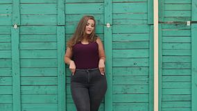Portrait of a girl model plus size on the background of a green wall. A young girl with a full figure walks in the Park in the summer against a green wooden stock footage