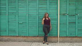 Portrait of a girl model plus size on the background of a green wall. Portrait of a young girl overweight in the city Park on the background of a green wooden stock video