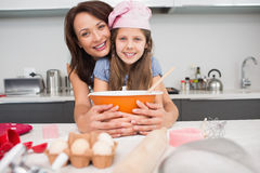 Portrait of a girl and mother preparing cookies in kitchen Stock Image