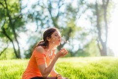 Portrait of a girl in nature blowing a dandelion royalty free stock photo