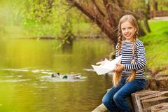 Portrait of girl near the pond holding paper boat Royalty Free Stock Photo