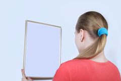 Portrait girl near a wall looking on empty frame. The studio on white background Royalty Free Stock Photos