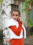 Portrait girl in orange under the birch tree Royalty Free Stock Image