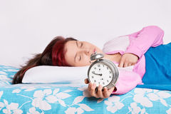 Portrait of a girl overslept with alarm clock in her hand royalty free stock photography