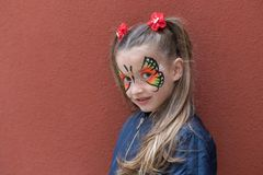 Portrait of girl with painted face. Girl with butterfly painted on face posing on the wall background stock photography