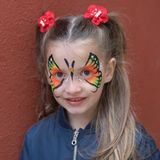 Portrait of girl with painted face. Girl with butterfly painted on face posing on the wall background stock photo