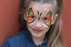 Portrait of girl with painted face. Close up of girl with butterfly painted on face royalty free stock photo