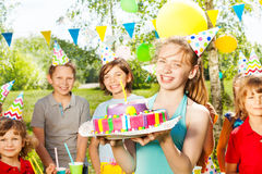 Portrait of girl in party hat holding B-day cake Royalty Free Stock Images
