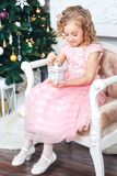 Portrait of a blonde girl in a pink dress against the backdrop of a Christmas tree with a white candlestick in the hands. Portrait of girl in a pink dress Royalty Free Stock Photos