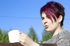 Portrait of a girl with pink hair drinking coffee stock image