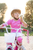 Portrait of girl in a pink safety helmet on her bike blowing a d Royalty Free Stock Photos