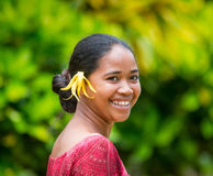 Portrait of a girl from the plantation Ylang Ylang. With Ylang Ylang flower in her hair. MADAGASCAR, NOSY BE - DECEMBER 6, 2014: Portrait of a girl from the Royalty Free Stock Photo
