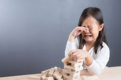 Portrait of girl play blocks wood game on wooden table backgroun stock photography