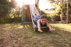 Portrait Of Girl Playing Outdoors At Home On Garden Slide Royalty Free Stock Photos