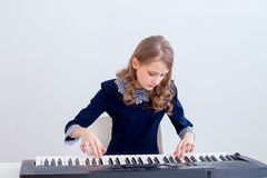 Girl playing synthesizer. A portrait of a girl playing on a synthesizer royalty free stock image