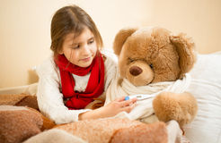 Portrait of girl playing with teddy bear in doctor and patient Stock Image