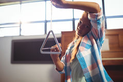 Portrait of girl playing triangle in classroom stock images