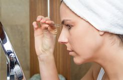Portrait of girl plucking eyebrows with tweezers Stock Photo