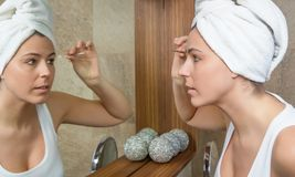 Portrait of girl plucking eyebrows with tweezers. Beautiful young woman plucking her eyebrows with tweezers in front of mirror on the bathroom Stock Image