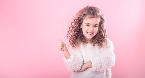 Portrait of girl pointing finger at up on pink. Portrait of a cute little smiling girl with curly hair pointing up on a pink background royalty free stock images