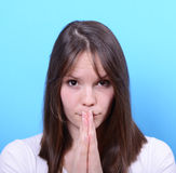Portrait of girl praying against blue background Royalty Free Stock Photos