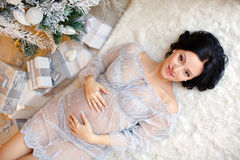 Portrait of a girl pregnant brunette in blue transparent dress i. N the interior decoration of the New Year and lying on the floor near the Christmas trees and Royalty Free Stock Images