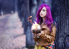 Portrait of a girl with purple hair. Freak girl with purple hair in a dark park Stock Photo