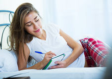 Portrait of girl putting dreams in notepad Royalty Free Stock Photo