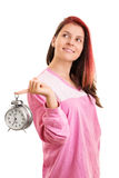 Portrait of a girl in pyjamas holding an alarm clock Royalty Free Stock Photo
