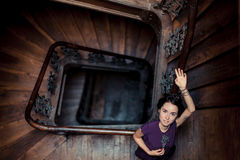 Portrait of a girl at railings in a dark interior,. Portrait of a girl in romantic style lying on a banisters at spiral staircase in a ray of light, with tatoo Royalty Free Stock Image