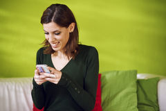 Portrait of girl reading sms on smarthphone at home Stock Photos