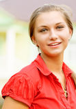Portrait of girl in red. Young beautiful woman laughs and looks in camera Royalty Free Stock Image