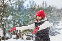 Portrait of girl in a red cap and warm jacket in the forest who have fun with snow royalty free stock photos