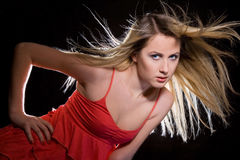 Portrait of girl in red dress. Portrait of blonde girl in red dress with flying hair stock images