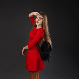 Portrait of a girl in a red dress with a black leather backpack Royalty Free Stock Photos