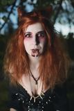 Portrait girl with red hair and bloody face vampire, murderer, psycho, halloween theme, bloody woman Royalty Free Stock Photo