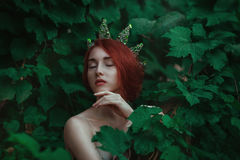 Portrait of a girl with red hair in a green leaves with a crown. On his head Stock Photo