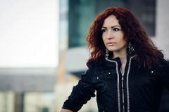 Portrait of a Girl with red hair. Standing on the building background stock images