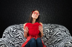 Portrait of a girl with a red heart cushion Stock Photos