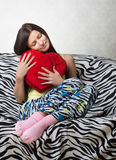 Portrait of a girl with a red heart cushion Stock Photography