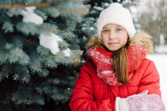 Portrait of a girl in a red jacket, near the green tree on the street Royalty Free Stock Photo