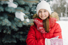 Portrait of a girl in a red jacket, near the green tree on the street Royalty Free Stock Images