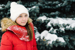Portrait of a girl in a red jacket, near the green tree on the street Royalty Free Stock Photography