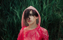 The portrait of girl in red raincoat under the rain. Royalty Free Stock Image
