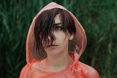 The portrait of girl in red raincoat under the rain. Sad and serious emotion on her face. She is upset because of the rain Close up Royalty Free Stock Images