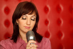 Portrait of girl in red shirt with microphone Royalty Free Stock Photos