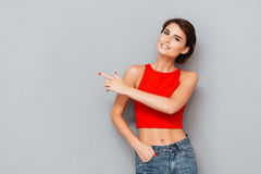 Portrait of a girl in red top pointing finger away Royalty Free Stock Images