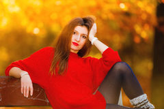 Portrait girl relaxing on bench in autumnal park. Royalty Free Stock Images